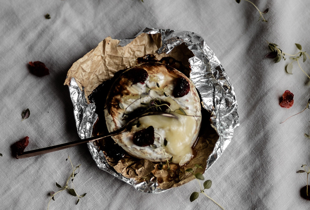 baked brie in foil with toppings and spoon