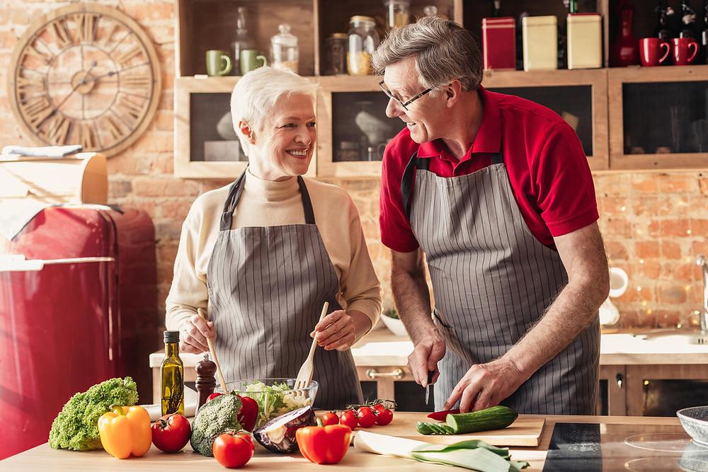 Elderly couple cooks in kitchen