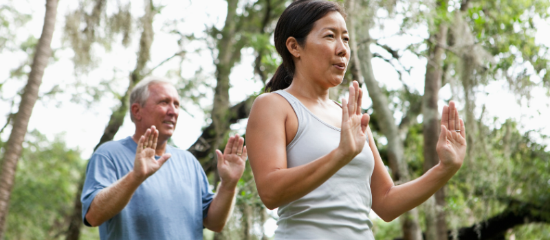 man and woman doing tai chi outside