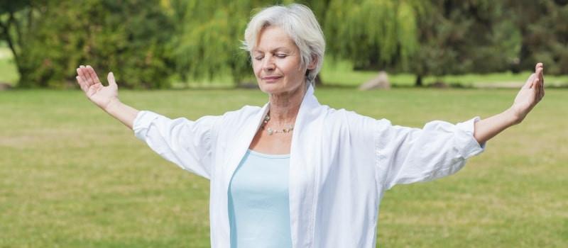 senior woman doing tai chi in park