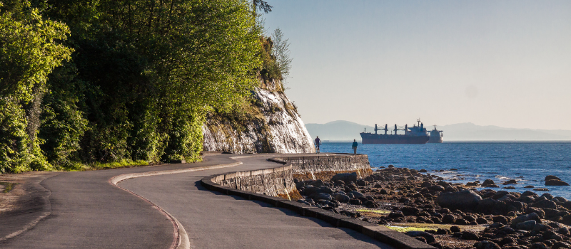 Seawall and rock wall under overcast, the curved lines of the path around Stanley Park with its pine tree woods and the waters of the Pacific Ocean. Vancouver, British Columbia, Canada
