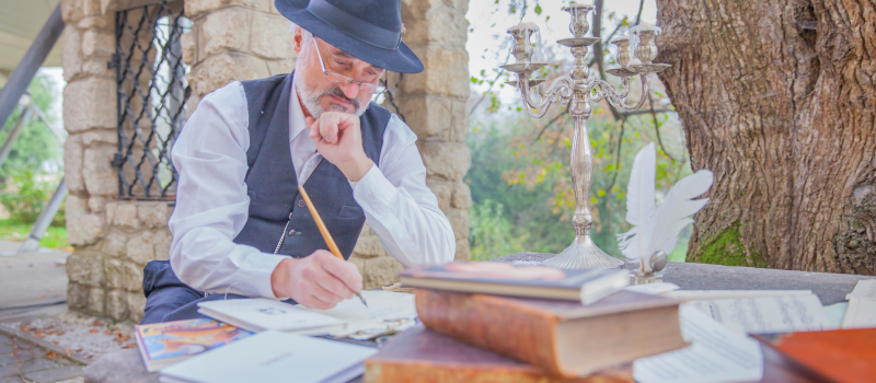 senior man outside writing in a notebook with books surrounding him