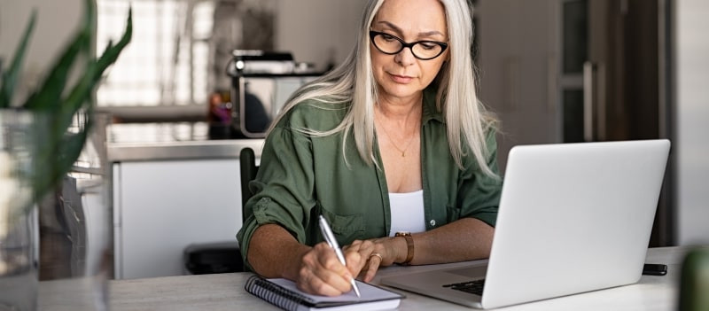 woman writing with laptop and book