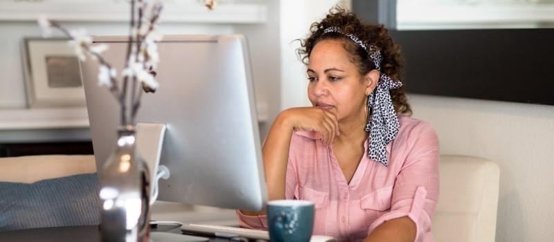 woman looking at computer screen thinking
