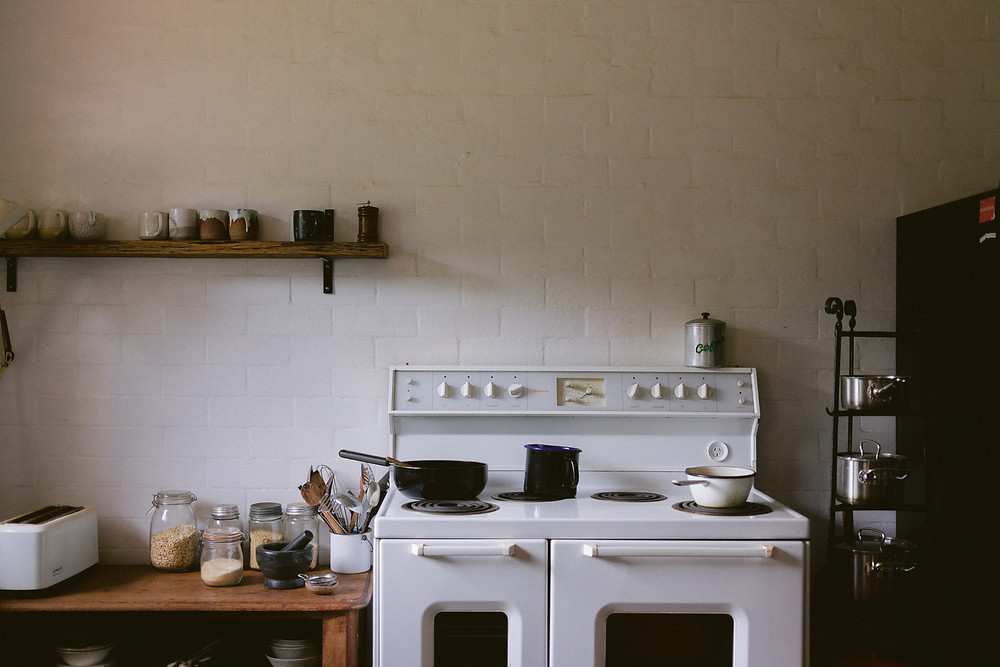 kitchen with white oven and pots and pans