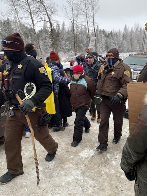 Michele is led away by multiple law enforcement personnel, all heavily bundled and masked against the cold and covid, while activists continue to protest in the background.
