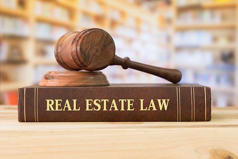 real estate law book with gavel ontop of it at Vasilic Law Firm
