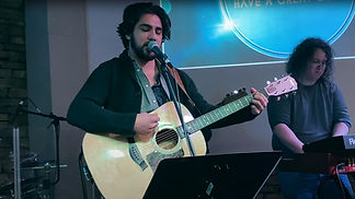 Worship leader plays guitar at a Life Spring Community Church service.