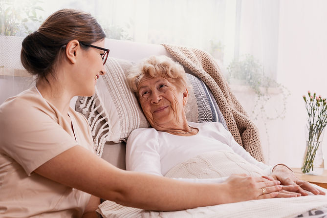Elderly woman in hospital bed with socia