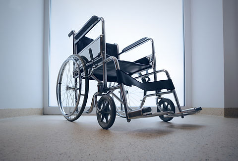 Empty wheelchair parked in hospital hall