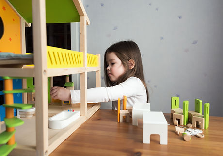 A little girl playing with dollhouse.jpg