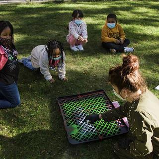 Artist spray painting with children on grass