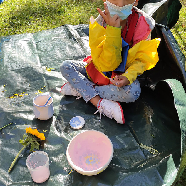 child with painting supplies on tarp