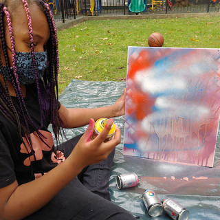 Child with spray paint and canvas