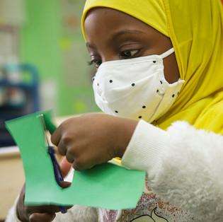 child cutting green paper