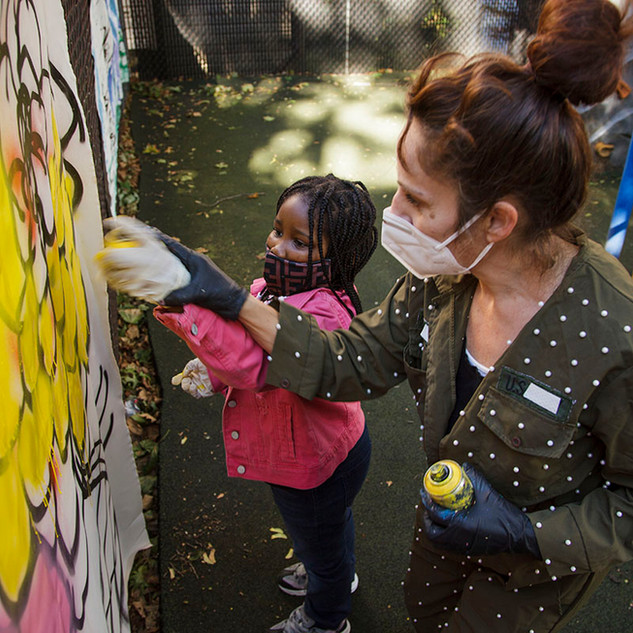 Artist and child spray painting