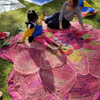 child and adult sitting on large crocheted flower