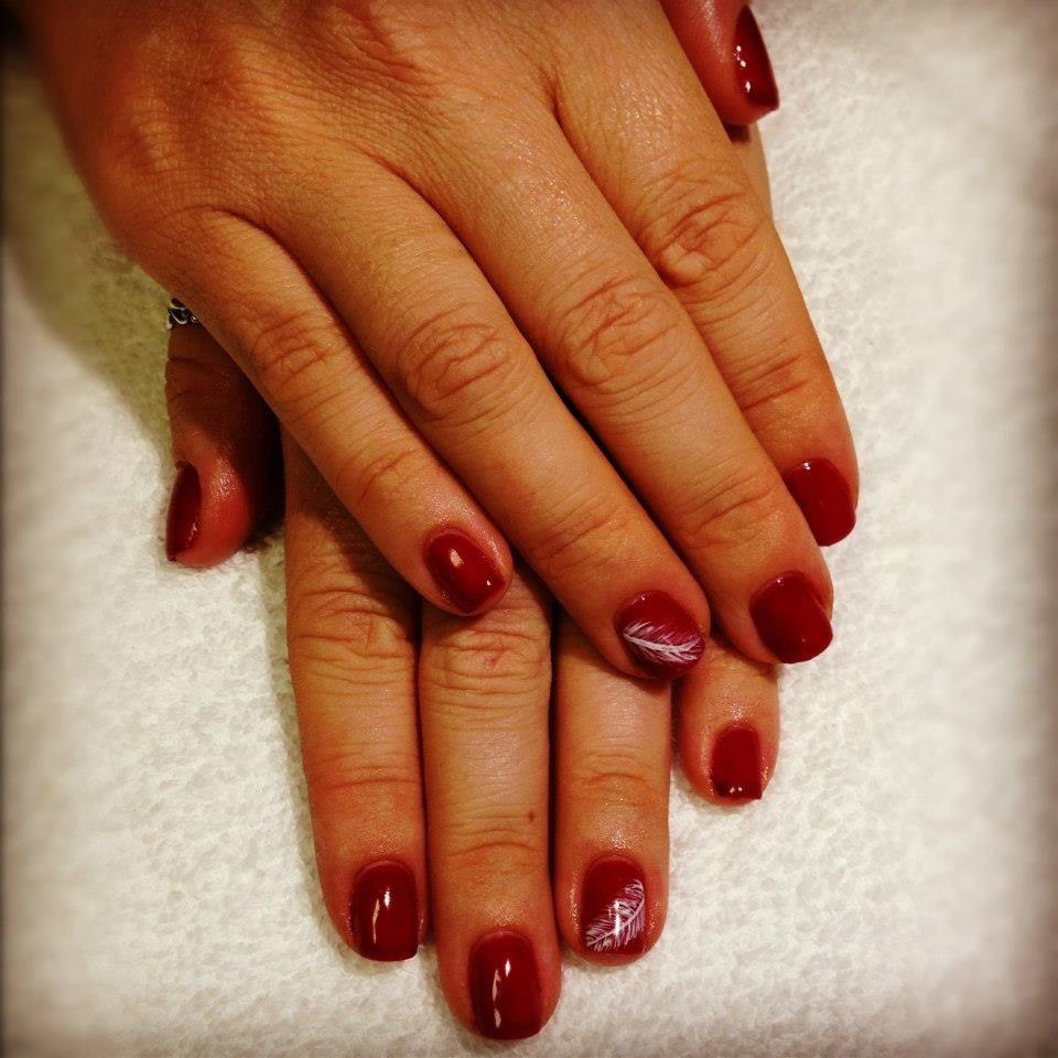 red nails with painted feather