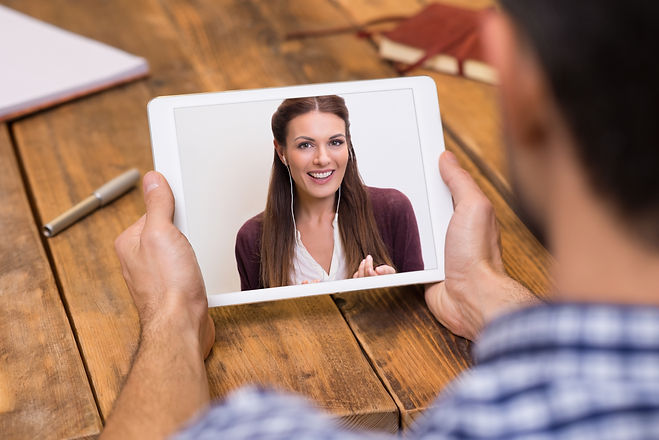 Closeup of a woman talking through video chat on tablet. Young man communicating with his girlfriend