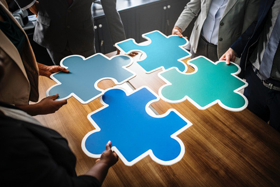 Business People Holding Pieces of a Puzzle