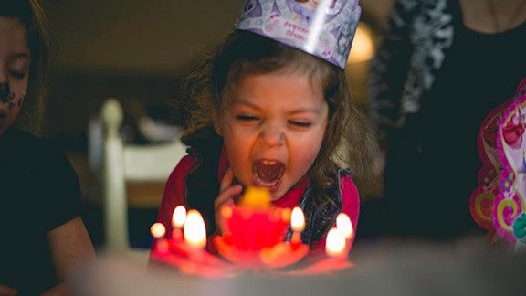 Little girl blowing out candles