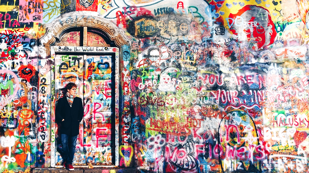 Man in front of graffiti wall