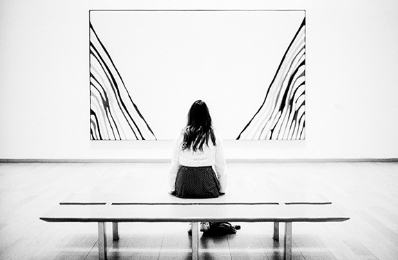 Woman Sitting On Bench Looking At Artwork