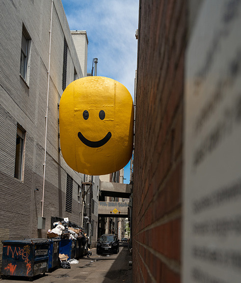 Yellow Smiley Face Artwork Between Two Buildings