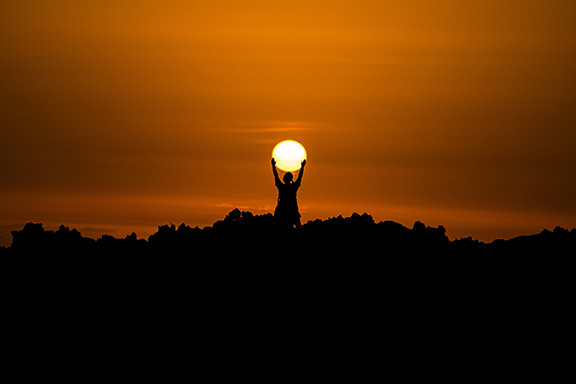Person holding the sun in their hands