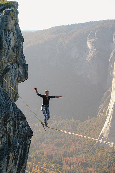 Person Walking on a tight rope across mountains