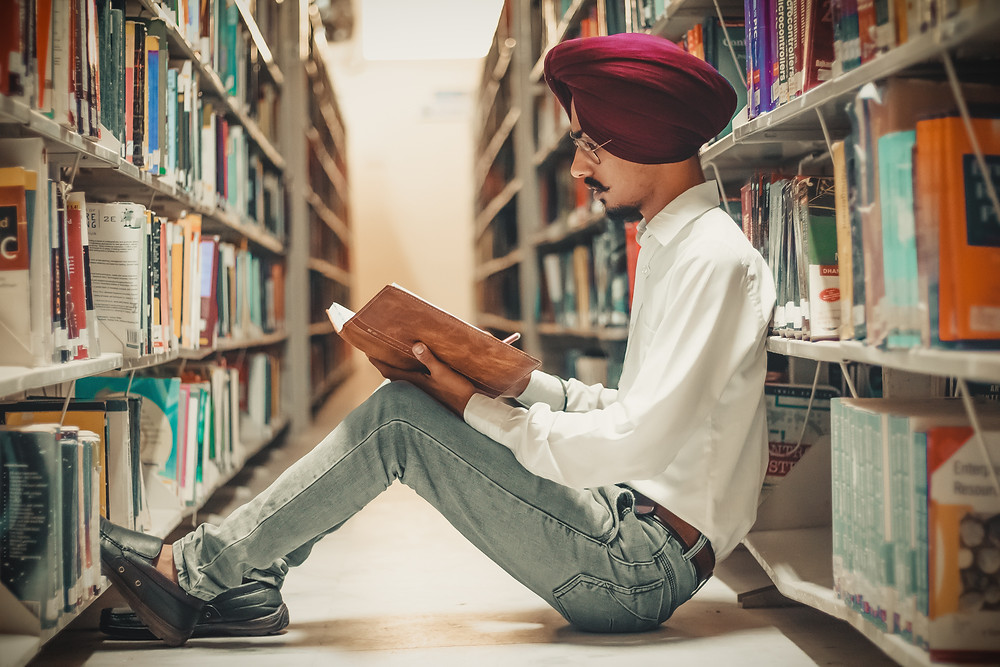Man sitting on floor in library reading