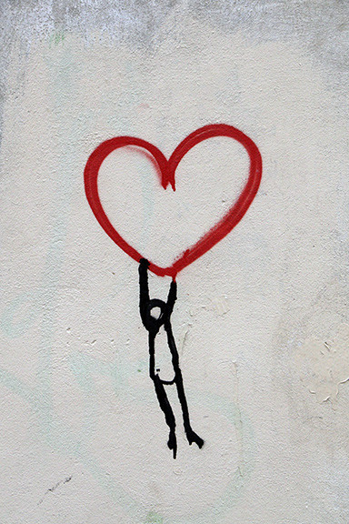 Man hanging from a heart drawing