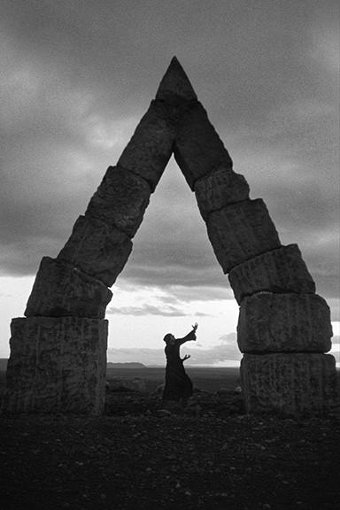 Person Meditating Under Stones