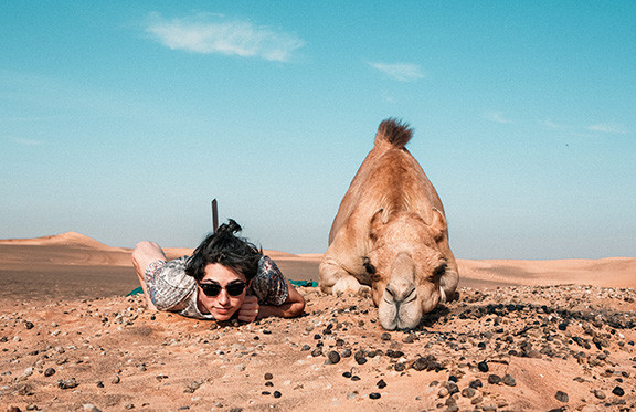 Woman posing for photo with a camel
