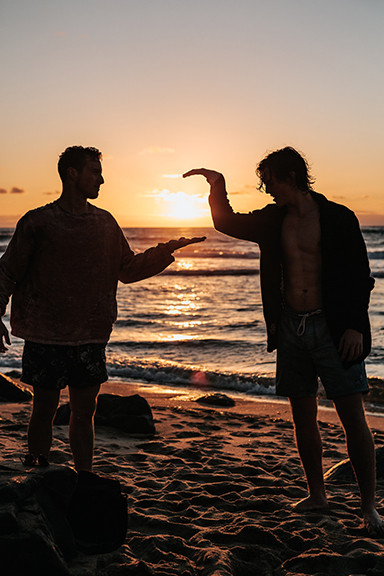 Two guys on beach high fiving