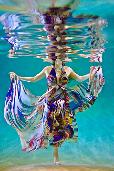 Woman wearing a colorful dress under water
