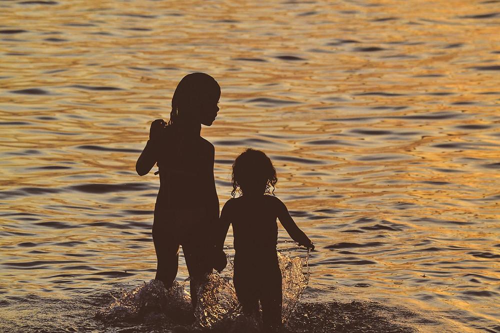 Silouette of two kids walking into ocean