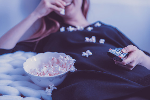 Girl In Bed with Remote Eating Popcorn