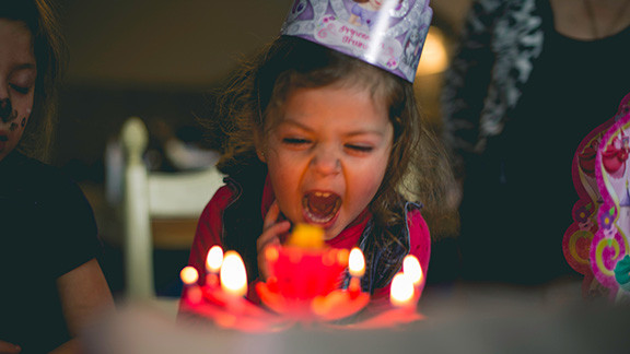 8 year old girl blowing out birthday candles