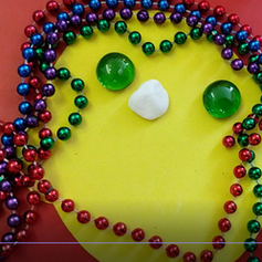 Beads, glass stones and chalk were used to create this smiley face