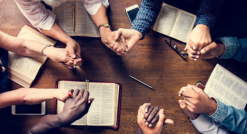 Group of people holding hands praying wo