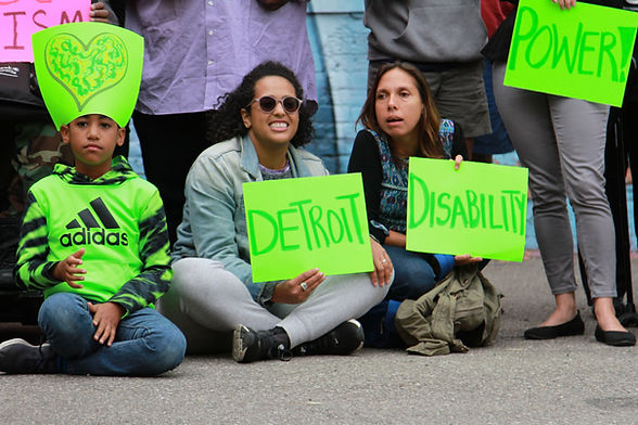 """DDP community members, some standing and some sitting on the ground holding bright signs that say """"Detroit"""", """"Disability"""" and  """"Power""""."""