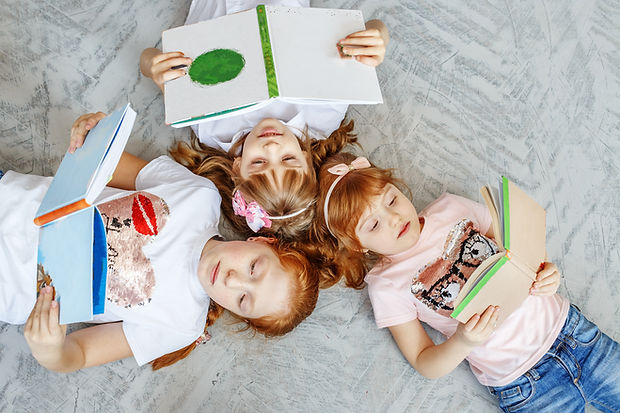 a-group-of-children-lays-on-the-floor-and-reads-bo-YQN4D7F.jpg
