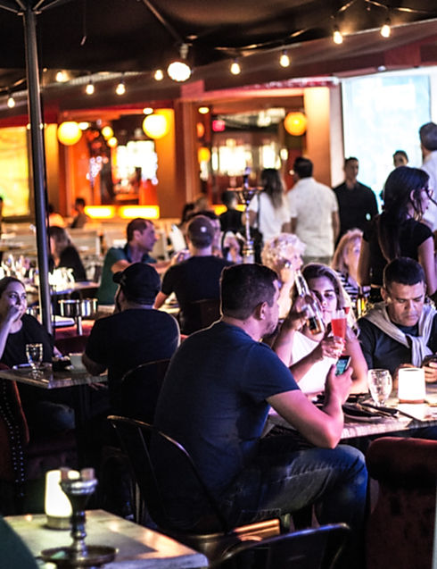 Crowd of patrons having drinks at 7 SPICES outddor lounge