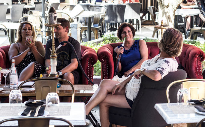 Group of contemporary people talking and smoking hookah on happy hour