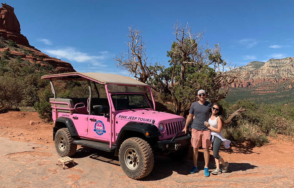 young couple with pink jeep while touring sedona arizona on the borken arrow jeep tour