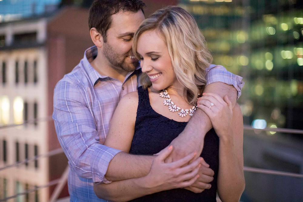 Beautiful couple in love at their fun engagement session with breathtaking scenic Pittsburgh backdrop from the rooftop of a parking garage