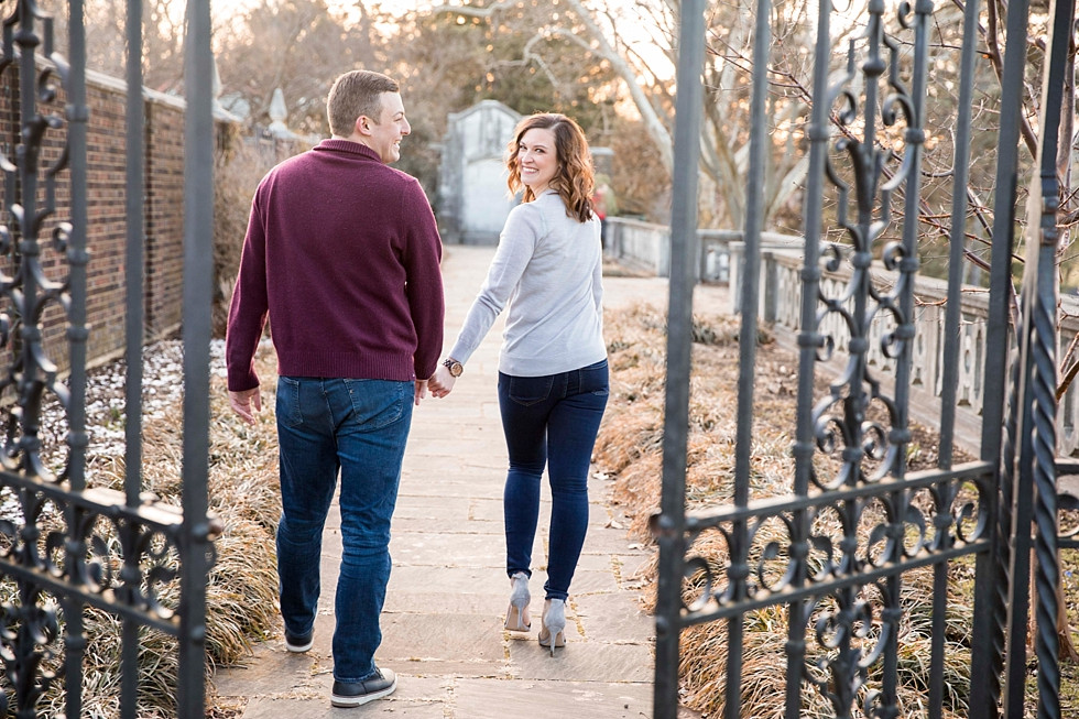 couple holding hands and smiling while walking through beauitiful pathway at the walled garden at mellon park