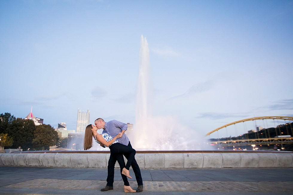 couple dipping and kissing in front of the fountain at Point State Park at dusk