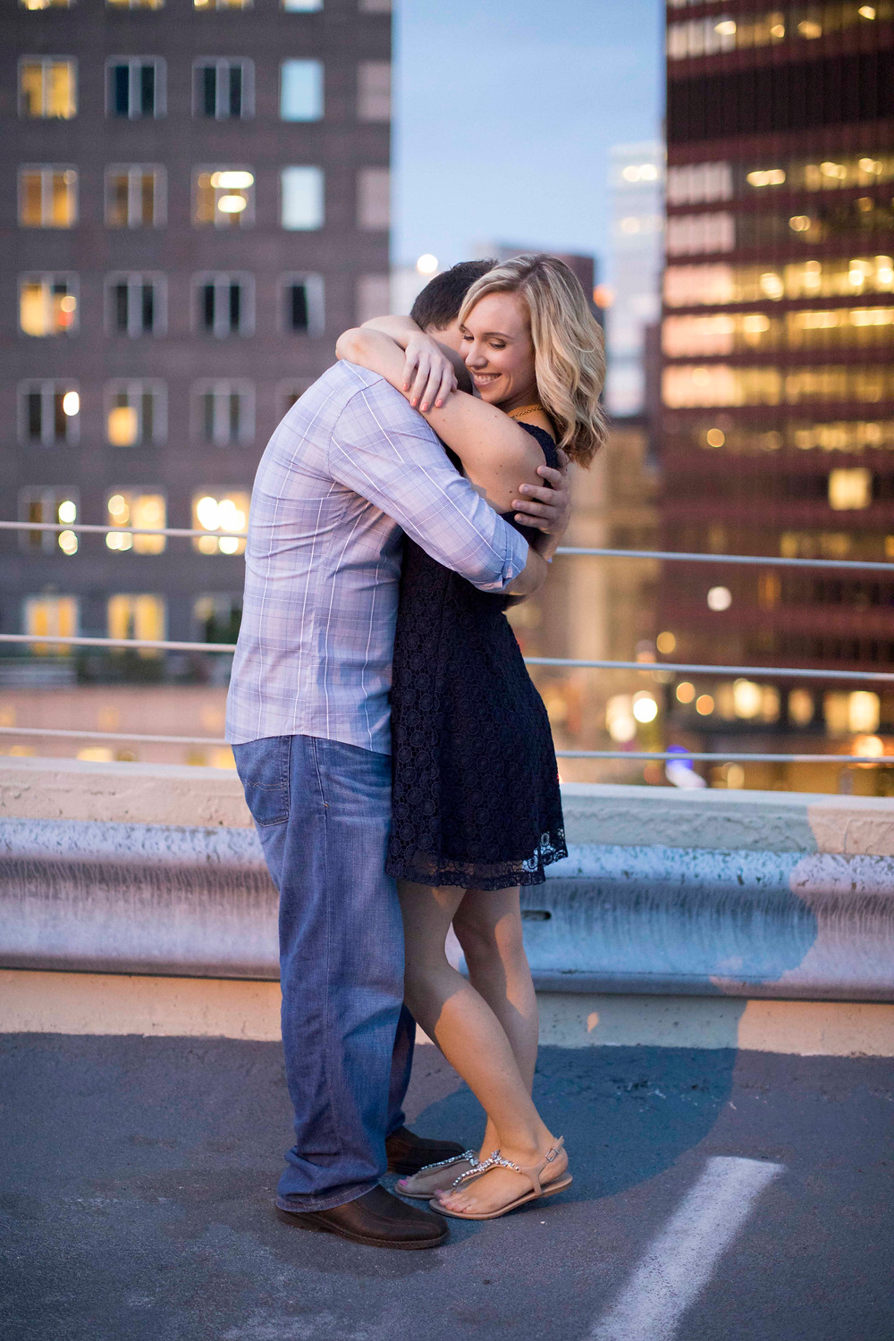 Unposed authentic couple in love hugging on top of a scenic parking garage in downtown Pittsburgh dring their urban engagement shoot